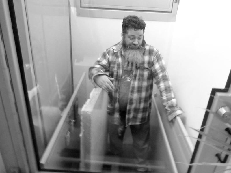 john inside an aquarium that floats abode walls up to the garage